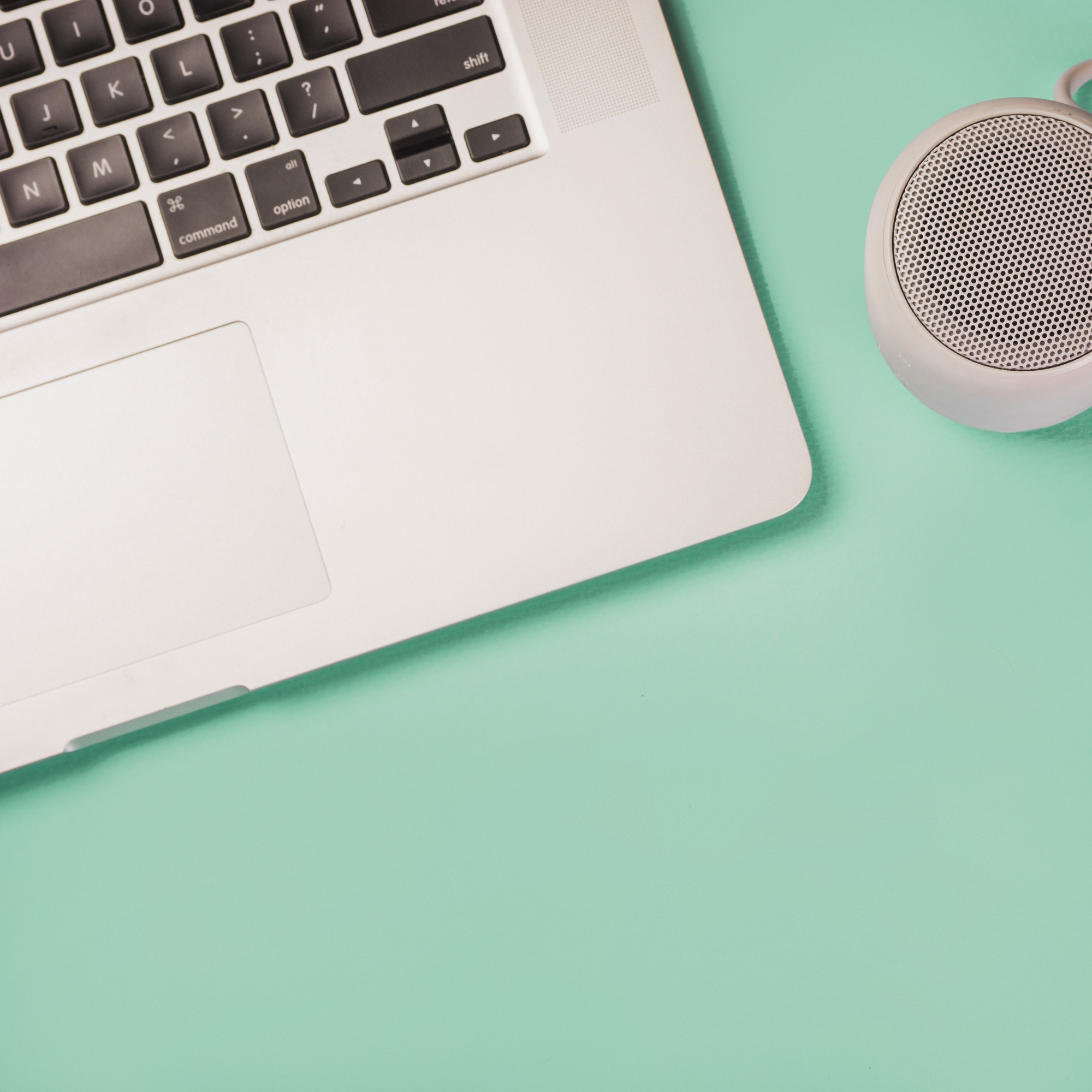 Close-up of bluetooth speaker and laptop on green background