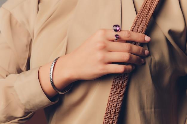 Закройте руки женщины в стиле бохо с серебряными украшениями.