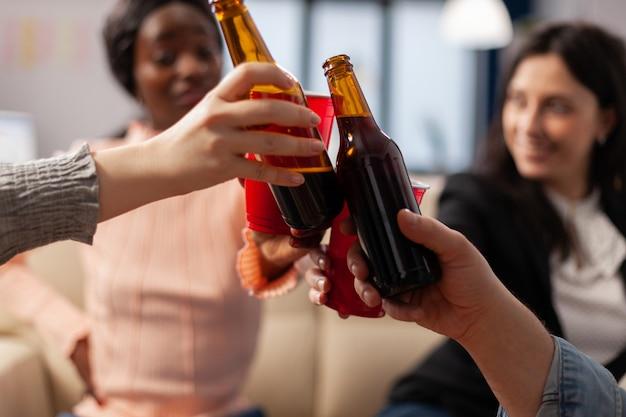 Закройте бутылки и чашки пива от веселых друзей после работы на корпоративе. многонациональная счастливая группа приветствует празднование развлечений в помещении с закусками, напитками и едой