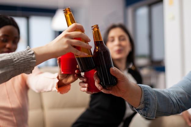 사무실에서 일한 후 쾌활한 친구들의 맥주 병과 컵을 닫습니다