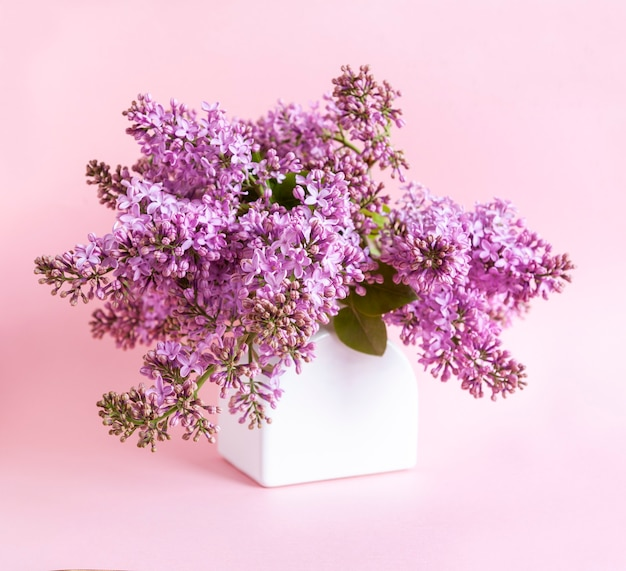 분홍색 배경에 흰색 꽃병에 신선한 향기 라일락 꽃다발 닫습니다.