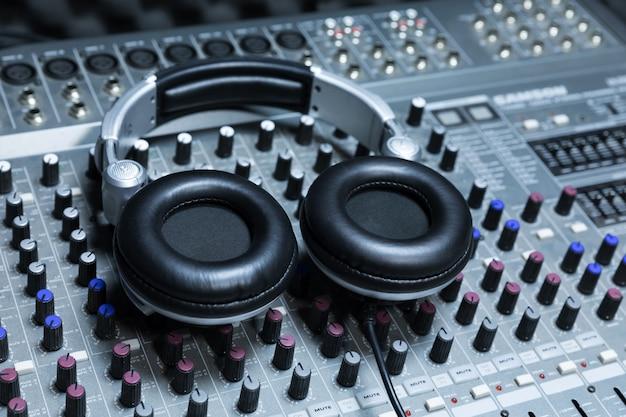 Крупный план пульта управления студии звукозаписи, наушники для профессионального диска, оборудование для студии звукозаписи, микшер и наушники dj