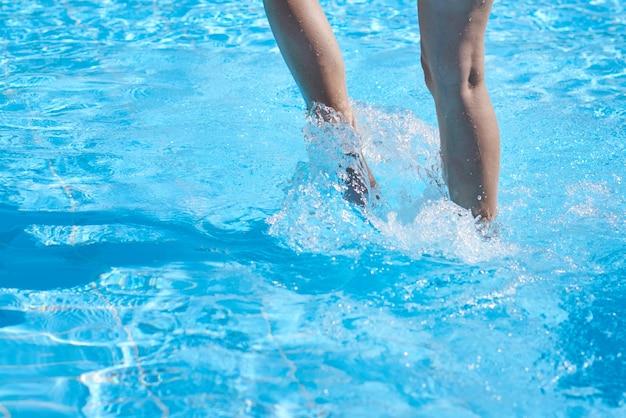 Закройте ноги мальчика в бассейне с вкраплениями. летний отдых