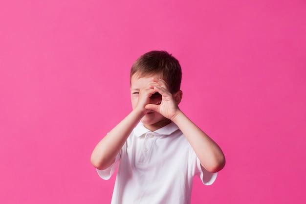 ピンクの壁の背景の上に双眼鏡として手を探している少年のクローズアップ