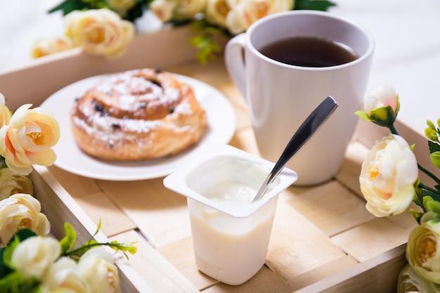 Закройте завтрак со сладкой булочкой, йогуртом и чаем на деревянном подносе