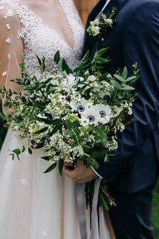 Крупным планом жених и невеста с букетом невесты