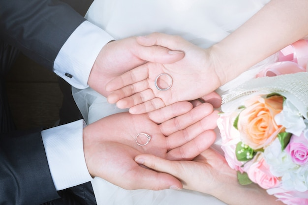 Крупным планом руки жениха и невесты с обручальными кольцами на ладонях рядом с букетом цветов