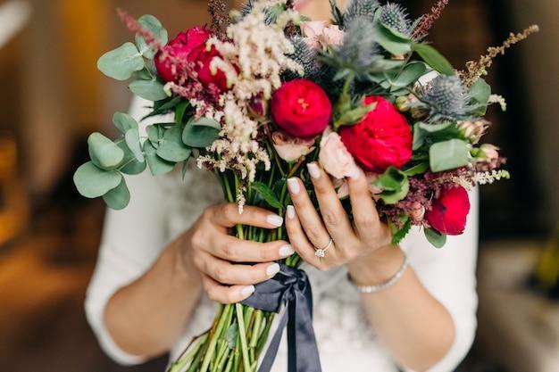 ブライダルブーケを持って花嫁のクローズアップ