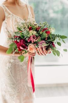 彼女のブライダルブーケを保持している花嫁のクローズアップ Premium写真