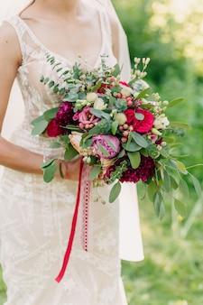 彼女のブライダルブーケを保持している花嫁のクローズアップ
