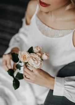ピンクのバラを持っている花嫁のクローズアップ Premium写真