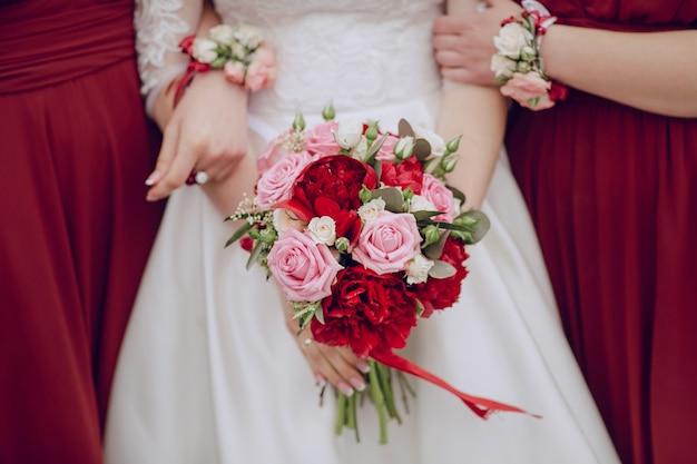Крупным планом невеста держит свадебный букет с подружками