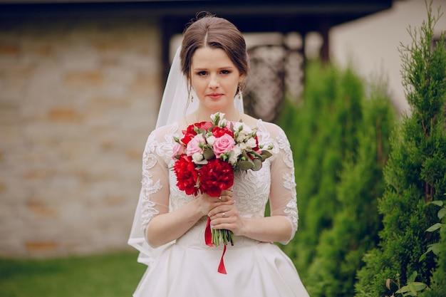Крупным планом невеста с букетом ее на открытом воздухе