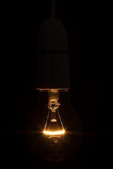 暗闇の中で明るい電球のクローズアップ