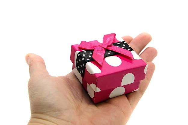 Крупный план ярко-розовой подарочной коробки в белый горошек с алой лентой на ладони на белом фоне