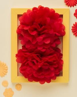 밝은 빨간 종이 꽃과 사진 프레임의 클로즈업