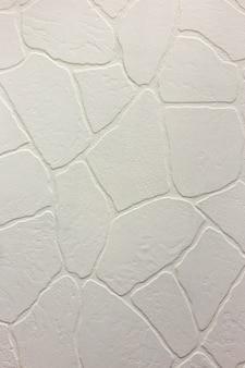 明るい白い漆喰の不均一な漆喰壁のクローズアップ。抽象的なテクスチャ、カオスコピースペースの背景。装飾的なグランジスペース。