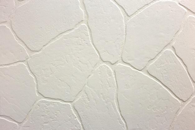 明るい白い漆喰の不均一な漆喰壁のクローズアップ。抽象的なテクスチャ、カオスコピースペース。装飾的なグランジスペース。