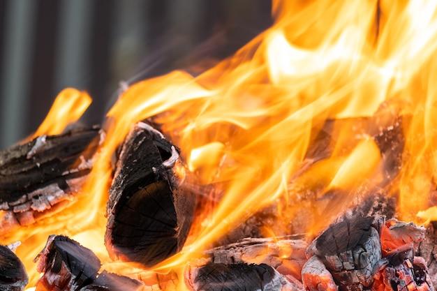 밤에 노란색 뜨거운 불길과 함께 밝게 타는 나무 통나무를 닫습니다.