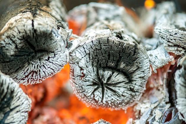 Закройте ярко горящих деревянных бревен с желтым горячим пламенем огня.