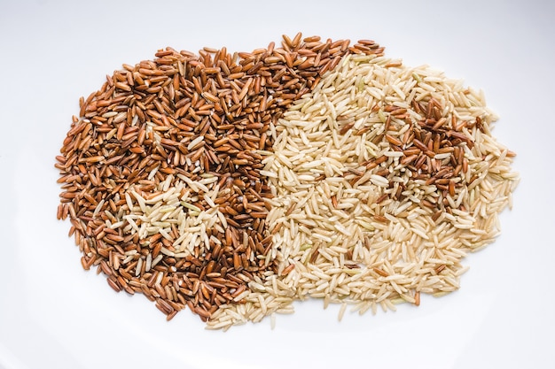 陰と陽を作成する白いプレートに混合された茶色と白の穀物のクローズアップ