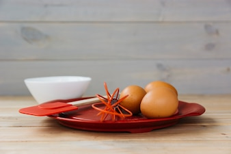Close-up of brown egg and whisk on plate
