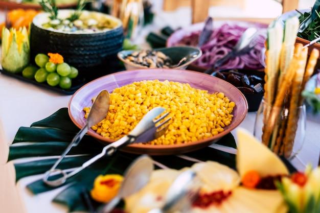 Крупный план кейтеринга на мероприятии с желтыми свежими вкусными кукурузными зернами