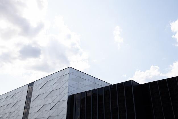 햇볕에 쬐 인 하늘을 검은 유리로 만든 벽과 조각에 삼각형 패턴과 둥근 개구부가있는 건물의 근접
