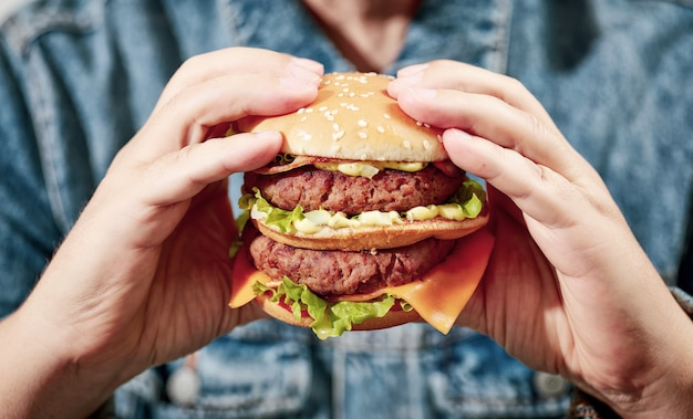 人間の手でハンバーガーのクローズアップ、フィルタリングされた画像