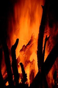 Крупным планом горящих поленьев в камине на черном фоне