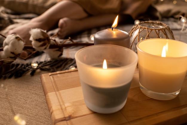 Крупный план горящих пахнущих свечей на деревянном подносе, поставленном на кровать для ароматерапии