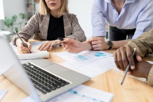会議でグラフやチャートを分析しながらノートパソコンでプレゼンテーションを見ているビジネス専門家のクローズアップ