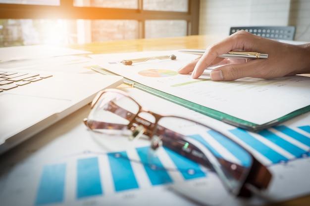 Закройте деловой человек рука ручка с ноутбуком и финансовые бумаги работают на деревянный стол с утренним светом