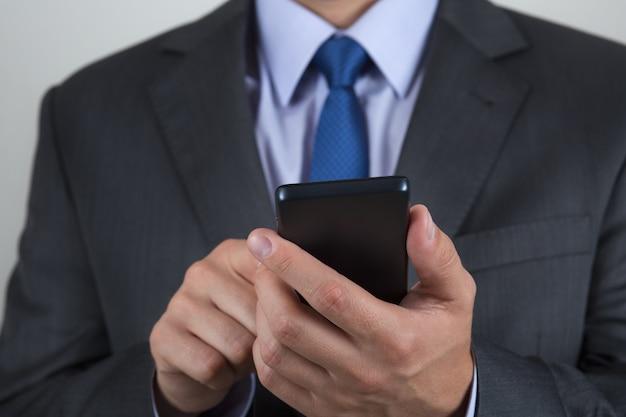 彼の携帯電話で何かを読んでビジネスマンの手のクローズアップ