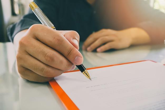 取引、ビジネス契約の詳細を作る契約を結ぶビジネスマンのクローズアップ。ビジネスマン、公式文書に署名する