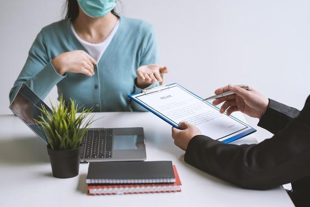 オフィスで求職者の履歴書を確認するためにペンを持っている事業主の手のクローズアップ。
