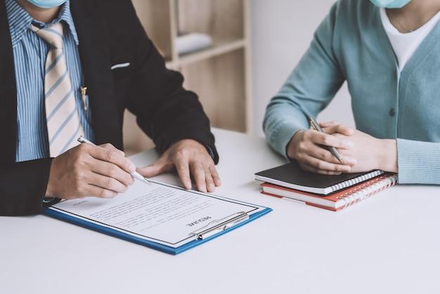 オフィスでの求職者の履歴書を確認するためにペンを持っている事業主の手のクローズアップ。