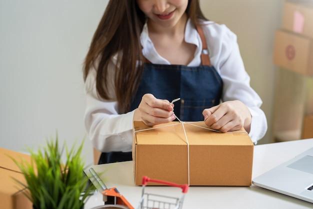 自宅の顧客に配達するための事業主の手梱包小包のクローズアップ。