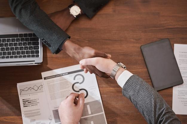 Крупный план деловых партнеров, пожимающих руки за столом во время работы с документами и ноутбуком