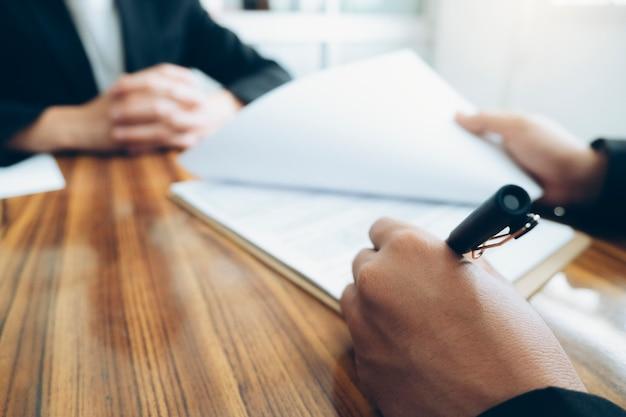 ビジネスパートナーのクローズアップは、会議で契約に署名します契約を交渉するビジネスマン