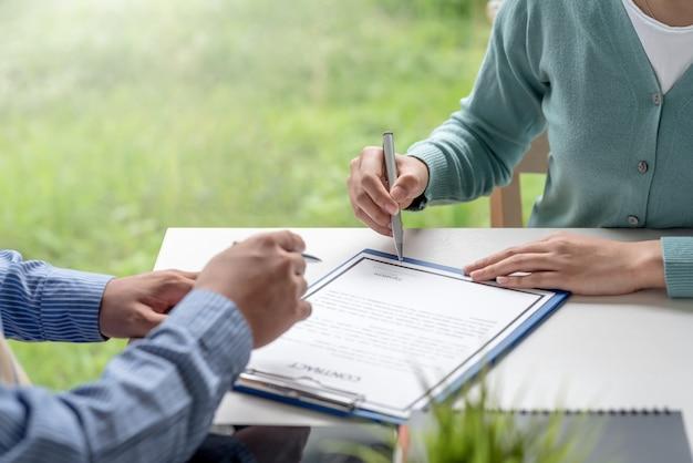 オフィスで一緒に契約を結ぶビジネスマンの手のクローズアップ。