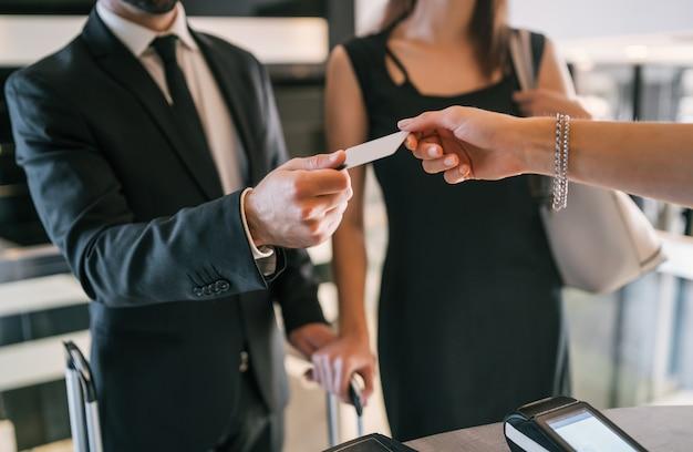 닫기 비즈니스 사람들이 리셉션 프런트 데스크에서 체크인시 카드 결제를합니다. 비즈니스 여행 개념.