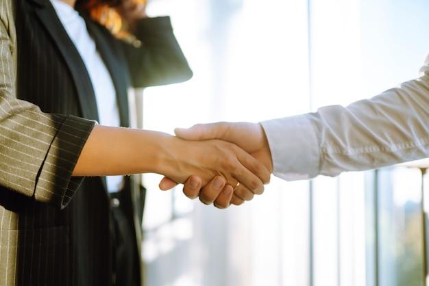 Закройте деловых людей, пожимая руки после встречи по контракту.