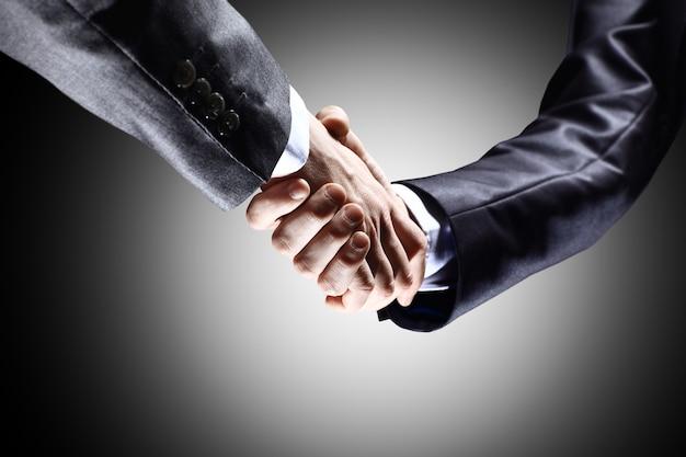 Крупный план деловых людей, пожимающих руки, чтобы подтвердить свое партнерство
