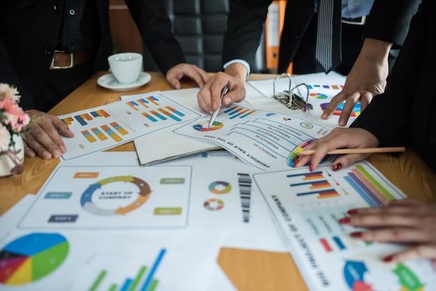 Закройте деловых людей, работающих с бизнес-документ во время обсуждения на совещании.