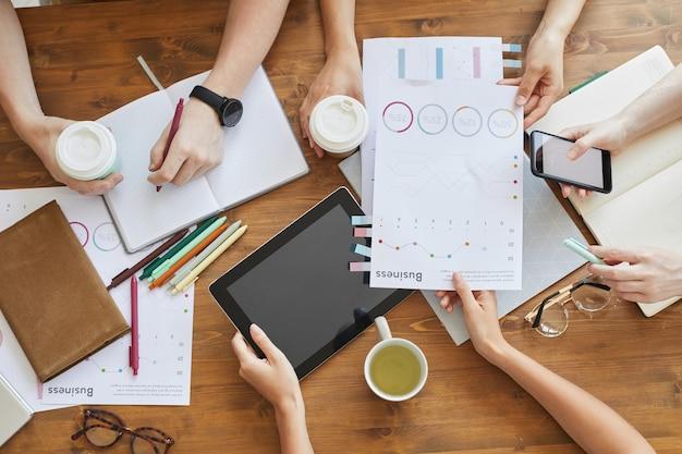 Крупный план деловых людей, работающих с документами диаграмм и планшетным пк за столом на встрече
