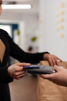 비즈니스 사무실에서 맛있는 맛있는 테이크아웃 음식을 지불하는 비접촉 기술이 있는 신용 카드를 사용하여 금융 및 비현금 거래를 하는 비즈니스 여성의 클로즈업.