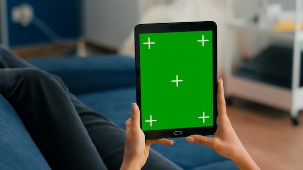 Закройте руки бизнес-леди, держа планшетный компьютер с макетом зеленого экрана дисплея ключа цветности, сидя на диване. фрилансер, использующий изолированное устройство с сенсорным экраном для просмотра социальных сетей