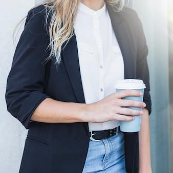 일회용 커피 컵을 손에 들고 비즈니스 여자의 근접 촬영