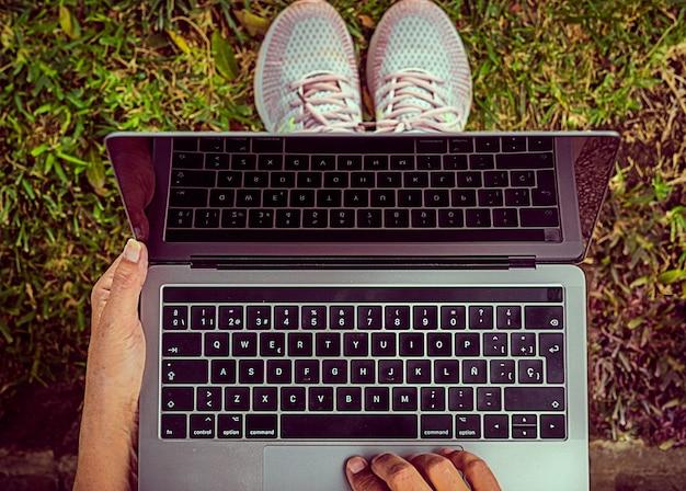 야외 공원에서 현대적인 휴대용 컴퓨터를 사용하는 비즈니스 우먼의 클로즈업. 디지털 유목 노동자 개념